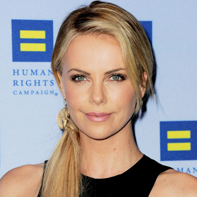 Charlize Theron says her dogs are helping her raise adopted son